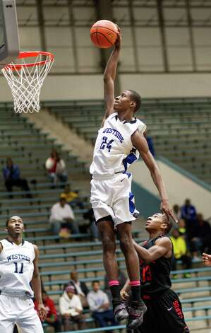 Westside's Rodrick Trimont (24) soars in for a dunk over Bellaire's Ryheem Mellone (13) in the fourth quarter to put the game out of reach during a high school basketball game between Westside and Bellaire at Delmar Fieldhouse, Friday, January 18, 2013. Westside defeated Bellaire 67-62. Photo: Bob Levey, Houston Chronicle / ©2013 Bob Levey
