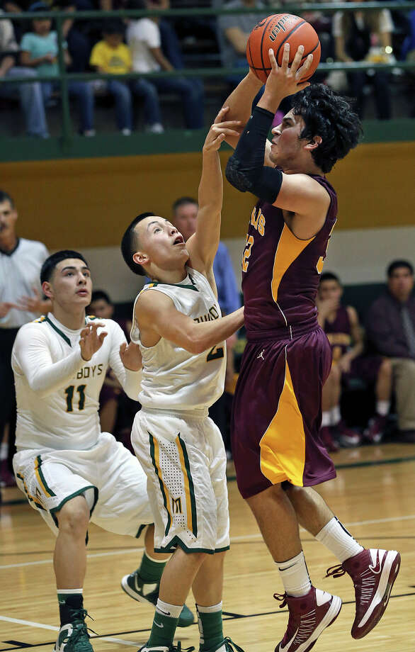 Brandon Ramon shoots for the Indians over Joey Villarreal as McCollum plays Harlandale in boys basketball at McCollum gym on January 18, 2013. Photo: Tom Reel, Express-News / ©2012 San Antono Express-News