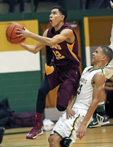 Indian guard Armando Guerrero gets in front of Tre Johnson at the hoop as McCollum plays Harlandale in boys basketball at McCollum gym on January 18, 2013. Photo: Tom Reel, Express-News / ©2012 San Antono Express-News