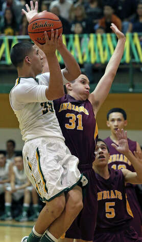 Cowboy forward Albert Marroquin puts up a shot against Austin Mendez as McCollum plays Harlandale in boys basketball at McCollum gym on January 18, 2013. Photo: Tom Reel, Express-News / ©2012 San Antono Express-News