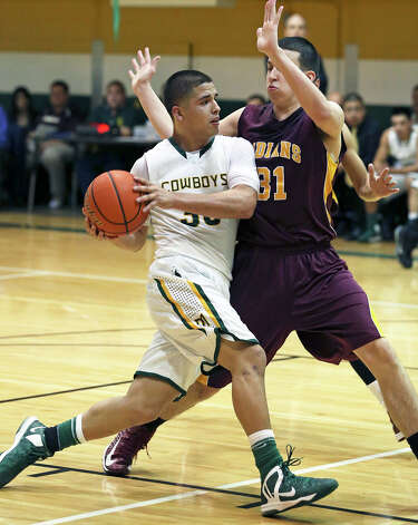Cowboys forward Albert Marroquin drives the lane against Austin Mendez as McCollum plays Harlandale in boys basketball at McCollum gym on January 18, 2013. Photo: Tom Reel, Express-News / ©2012 San Antono Express-News