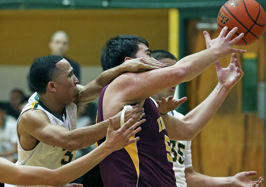 Indian center Jacob Rios has to wrestle for a rebound as Alonzo Guerra (3) and Albert Marroquin chop on him as McCollum plays Harlandale in boys basketball at McCollum gym on January 18, 2013. Photo: Tom Reel, Express-News / ©2012 San Antono Express-News