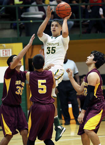 Albert Marroquin takes a shot in a crowd for the Cowboys as McCollum plays Harlandale in boys basketball at McCollum gym on January 18, 2013. Photo: Tom Reel, Express-News / ©2012 San Antono Express-News