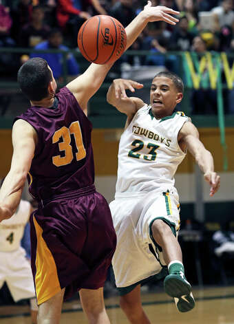 Cowboy forward Tre Johnson whips the ball past Austin Mendez as McCollum plays Harlandale in boys basketball at McCollum gym on January 18, 2013. Photo: Tom Reel, Express-News / ©2012 San Antono Express-News