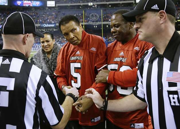Muhammad Ali, center, and NFL great Tom Jackson, right, shakes hands with officials prior to the coin toss before the Sugar Bowl NCAA college football game Wednesday, Jan. 2, 2013, in New Orleans. (AP Photo/POOL, Bill Haber) Photo: Bill Haber, Associated Press