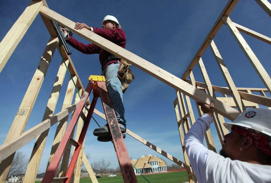 Manuel Rubio and Richard Gonzales build the frame of a home in a Sugar Land subdivision. Photo: Mayra Beltran, Staff / © 2012 Houston Chronicle