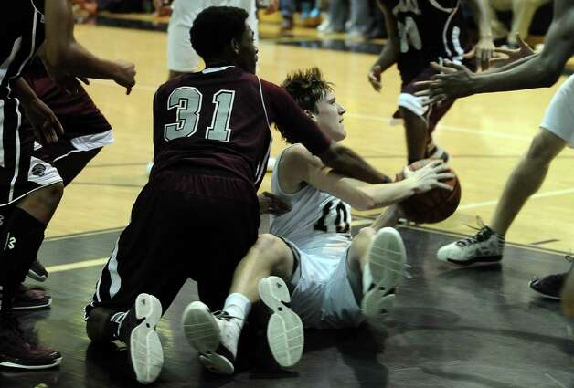 Central player Michael Jacquet, #31, fights for the ball with Nederland guard Zach English, #10, during the Nederland High School boys basketball game against Central High School on Friday, January 18, 2013.  Central won over Nederland 50 - 40. Photo taken: Randy Edwards/The Enterprise
