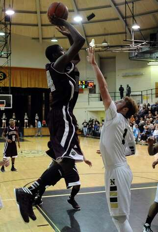 Central player E'Torrion Wilridge, #24, puts it up for two during the Nederland High School boys basketball game against Central High School on Friday, January 18, 2013.  Central won over Nederland 50 - 40. Photo taken: Randy Edwards/The Enterprise