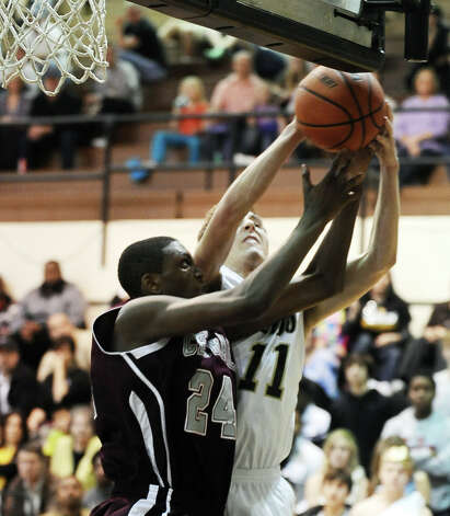 Nederland player Jared Lorimier, #11, snags a rebound over E'Torrion Wilridge, #24, during the Nederland High School boys basketball game against Central High School on Friday, January 18, 2013.  Central won over Nederland 50 - 40. Photo taken: Randy Edwards/The Enterprise