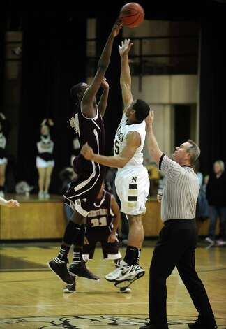 A Central player wins the tip during the Nederland High School boys basketball game against Central High School on Friday, January 18, 2013.  Central won over Nederland 50 - 40. Photo taken: Randy Edwards/The Enterprise