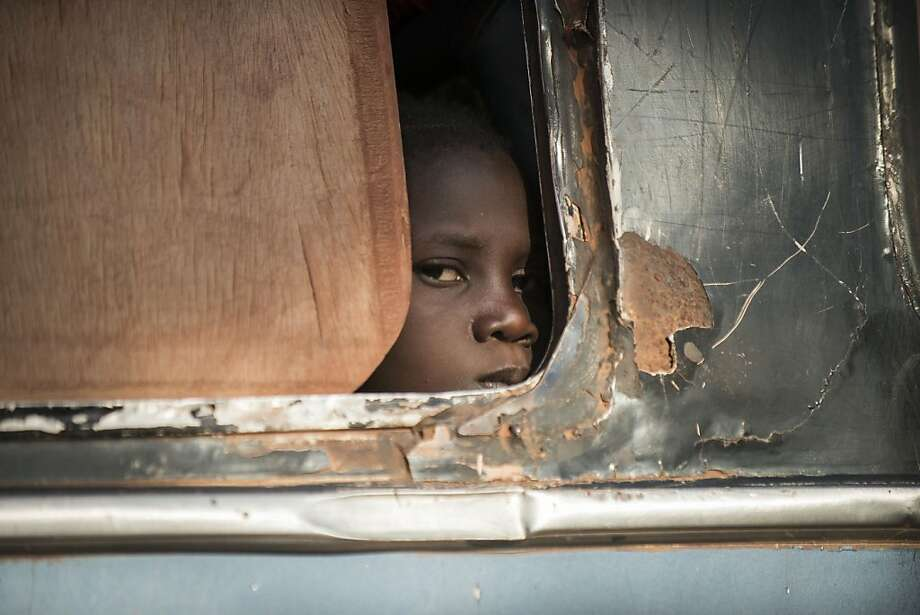 A Malian girl looks out from a bus as Malian army soldiers prepare to check the vehicule and passengers at a checkpoint in the city of Niono, on January 18, 2013. France now has 1,800 troops on the ground in Mali, inching closer to the goal of 2,500 it plans to deploy in its African former colony, Defence Minister Jean-Yves Le Drian said today. That was 400 more than a day earlier, said the minister as he met with French special forces in the western port of Lorient. The troops have been sent to help the Malian army regain control of the north from Islamist groups. Photo: Fred Dufour, AFP/Getty Images
