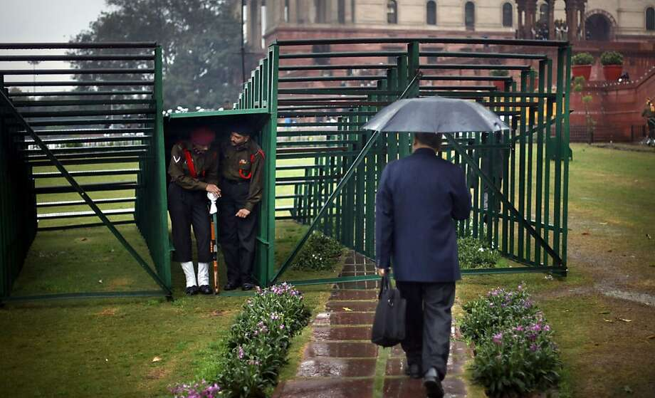 An Indian man walks past Indian security personnel taking shelter under temporary stands as it rains in New Delhi, India, Friday, Jan. 18, 2013. Heavy rains and hailstorm lashed the national capital, causing traffic jam and water logging in several areas. Photo: Altaf Qadri, Associated Press