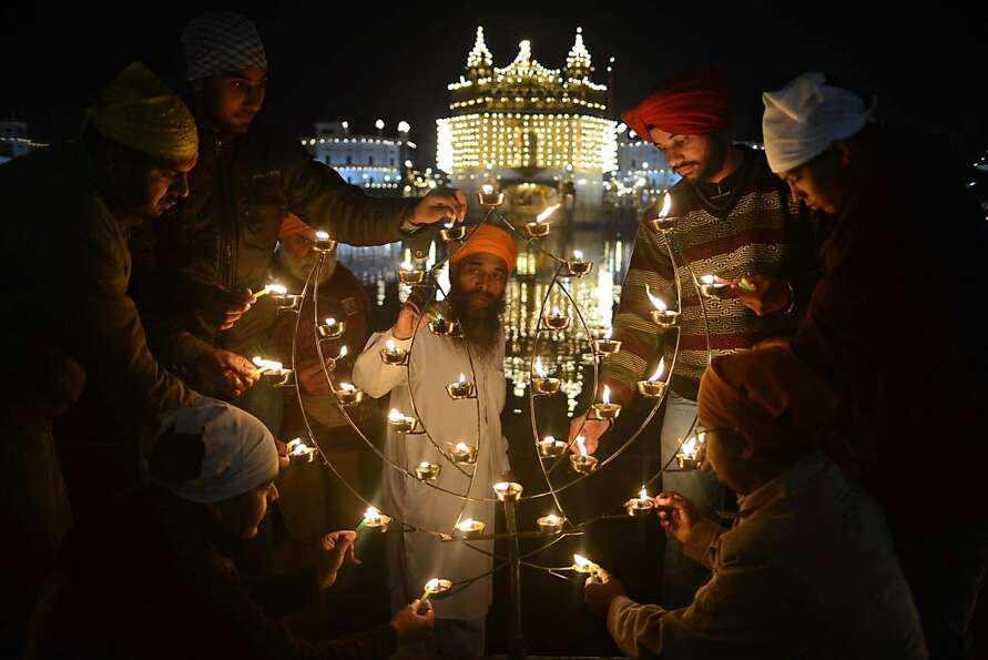 Indian Sikh devotees pose as they light lamps at the Golden Temple in Amritsar  on January  18, 2013