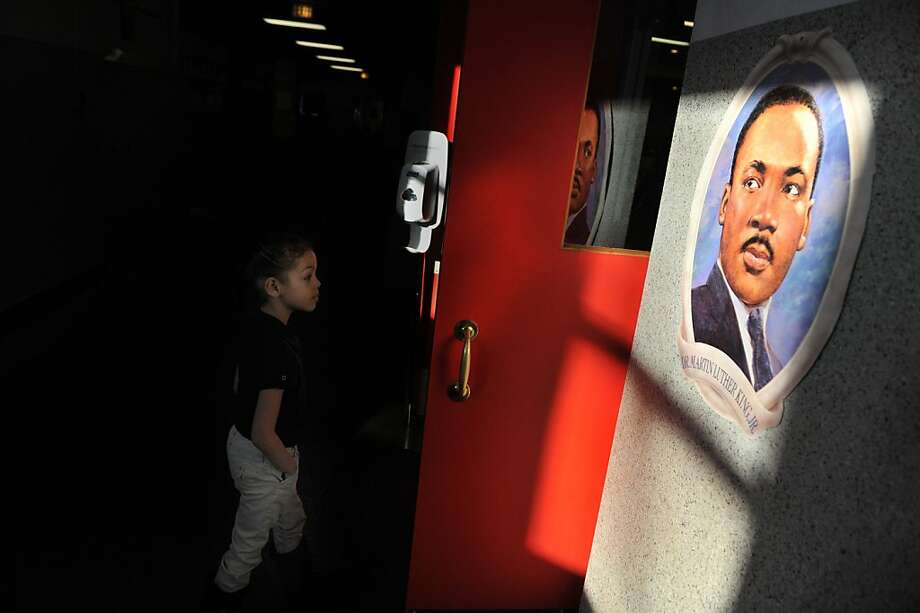 "A student looks at an image of Martin Luther King Jr., as they enter the auditorium at Joshua Academy before the start of the ""Living the Dream"" program put on by first grade students at the school in Evansville, Ind. Friday, Jan. 18, 2013.   The event was part of a celebration of the life of King, and the students will perform the program again Monday, on Martin Luther King Jr. Day.  Photo: Jason Clark, Associated Press"