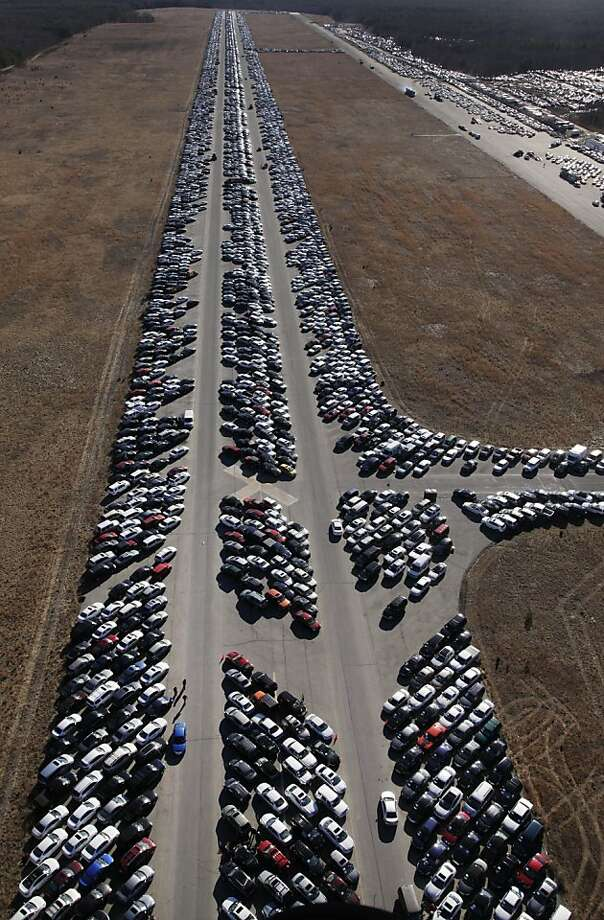 This Friday, Jan. 18, 2013 aerial photo shows thousands of cars which were damaged in the Oct. 29, 2012 Superstorm Sandy and stored on the runways at Calverton Executive Airpark in Calverton, N.Y. Environmentalists are decrying the placement of the 18,000 damaged automobiles at the defunct defense plant on eastern Long Island near the environmentally protected Pine Barrens. The town supervisor in Riverhead disputes the idea that there is any hazard. The town leased the runways to salvage companies and could reap up to $2.7 million under the lease agreement.  Photo: Mark Lennihan, Associated Press