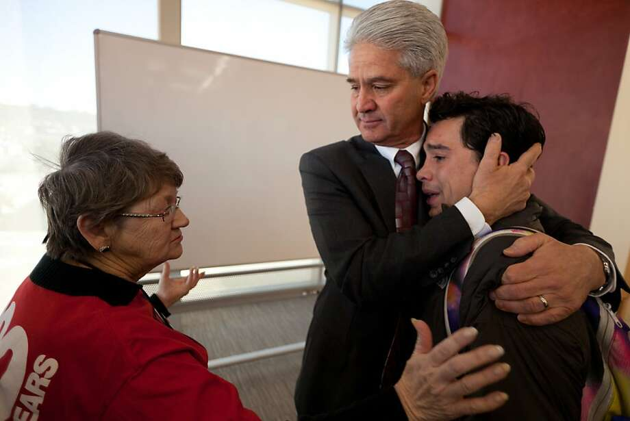 Brody Mikesell, student body president and student representative on the Dixie State College Board of Trustees, right, gets a hug from the board's chairman, Steven Caplin, and further consolation from Dixie State alumni Linda Johnston, left, after Mikesell had voiced his personal opposition to the board's decision on the name Dixie State University, Friday, Jan. 18, 2013, in St. George, Utah.  Mikesell cast his vote in favor of the name in an effort to promote student unity. Photo: Jud Burkett, Associated Press