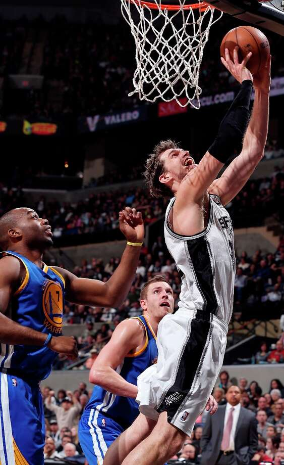 The Spurs' Tiago Splitter shoots around Golden State Warriors' Carl Landry (left) and Golden State Warriors' David Lee during second half action Friday Jan. 18, 2013 at the AT&T Center. The Spurs won 95-88. Photo: Edward A. Ornelas, San Antonio Express-News / © 2012 San Antonio Express-News