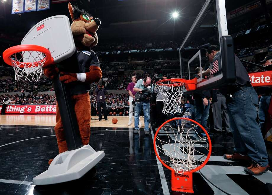 The San Antonio Spurs Coyote (left) plays to the crowd as workers tighten the rim before second half action against the Golden State Warriors Friday Jan. 18, 2013 at the AT&T Center. The Spurs won 95-88. Photo: Edward A. Ornelas, San Antonio Express-News / © 2012 San Antonio Express-News