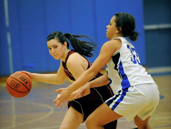 Colonie's Julia Dyer ,left, is defended by Shaker's Merrick Rowland during their basketball game in