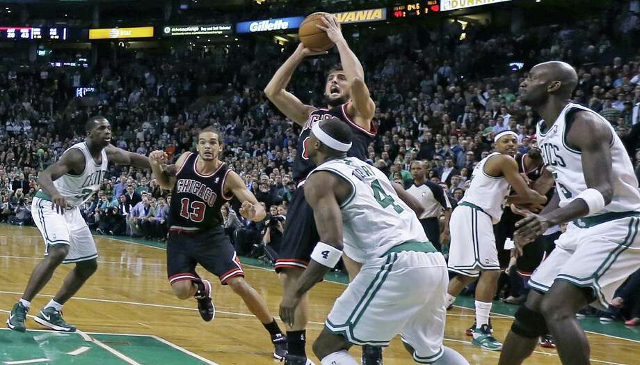 Chicago Bulls guard Marco Belinelli, center, puts up the game-winning basket in the final seconds of overtime against the Boston Celtics during an NBA basketball game in Boston on Friday, Jan. 18, 2013. The Bulls beat the Celtics 100-99. (AP Photo/Charles Krupa) Photo: Charles Krupa