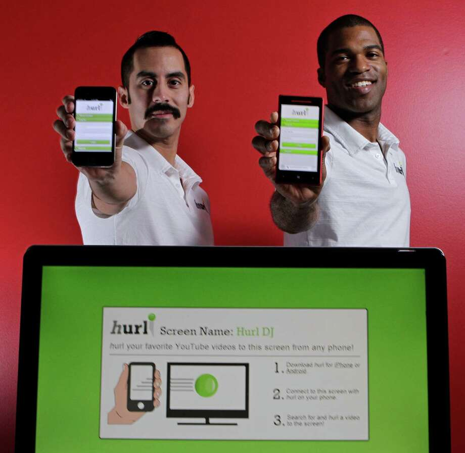Naaman Esquivel, left, and Lawrence Johnson created the Hurl app, which allows users to launch videos from their phones onto any screen that's wired to the Internet. Photo: Melissa Phillip, Staff / © 2013 Houston Chronicle