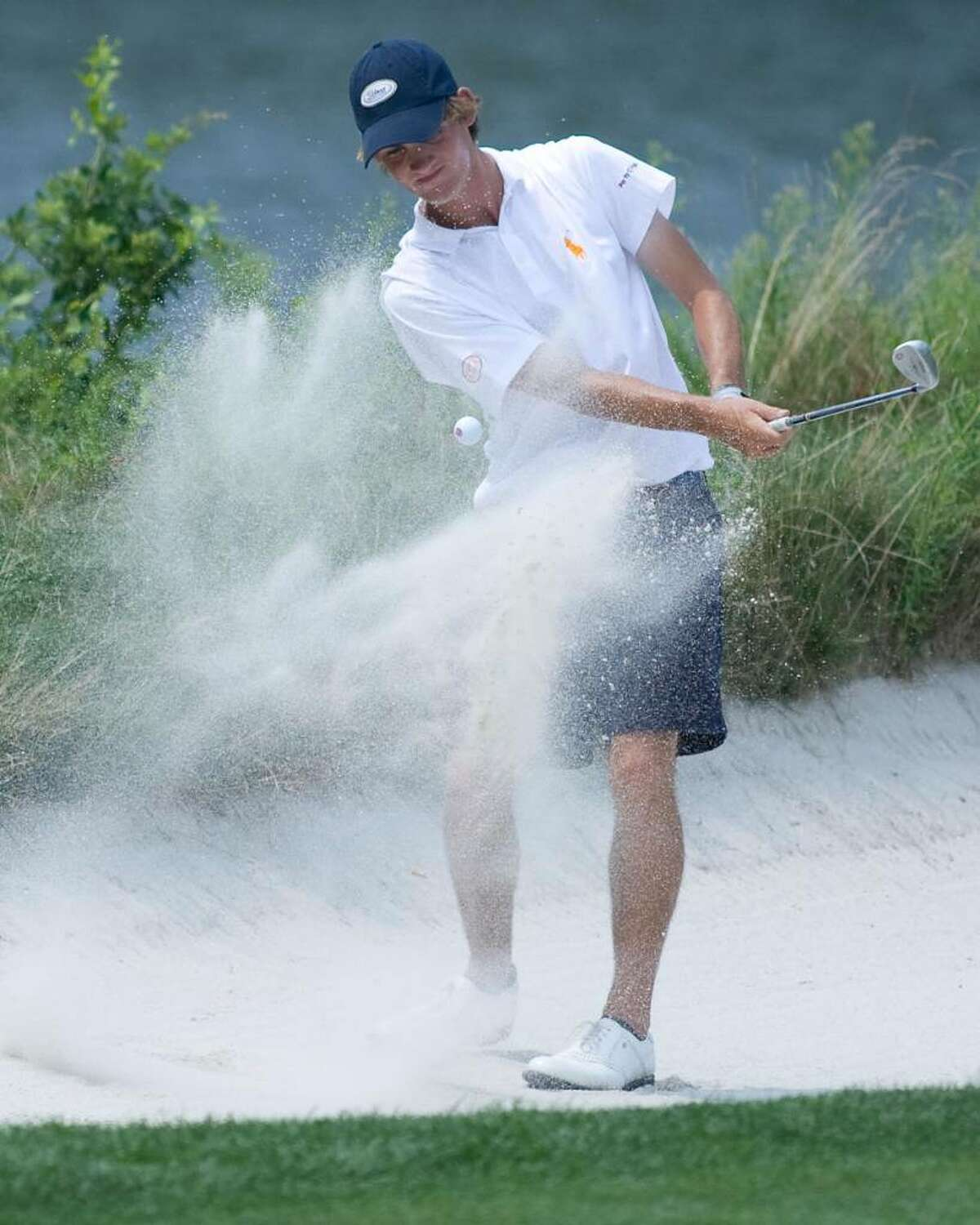 Chris Wiatr of Woodbury blasts out of the bunker to within two feet of the 12th hole during play in the AJGA Northeast Open tournament Tuesday at Richter Park Golf Course. August 2009