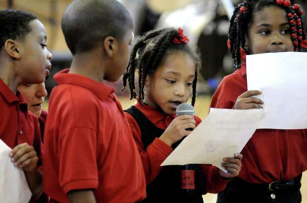 Kindergartener Karina Abrahams reads part of the timeline of Dr.King's life during a Remembering and Celebrating Dr. Martin Luther King Jr. program at the Albany Community Charter School on Friday Jan.18,2013 in Albany, N.Y. (Michael P. Farrell/Times Union) Photo: Michael P. Farrell