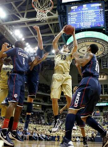 Pittsburgh's Steven Adams (13) goes up for a shot between UConn's DeAndre Daniels (2) and Omar Calhoun (21) during the first half of an NCAA college basketball game, Saturday, Jan. 19, 2013, in Pittsburgh. (AP Photo/Keith Srakocic)