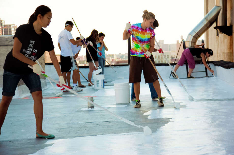 Some 90 percent of U.S. buildings have dark-colored roofs which, when exposed to full sun can increase in temperature by as much as 90 °F. A white roof typically increases temperatures only 10 to 25 degrees above ambient air temperatures during the day. Pictured: The White Roof Project at work. Photo courtesy of the White Roof Project Photo: Contributed Photo