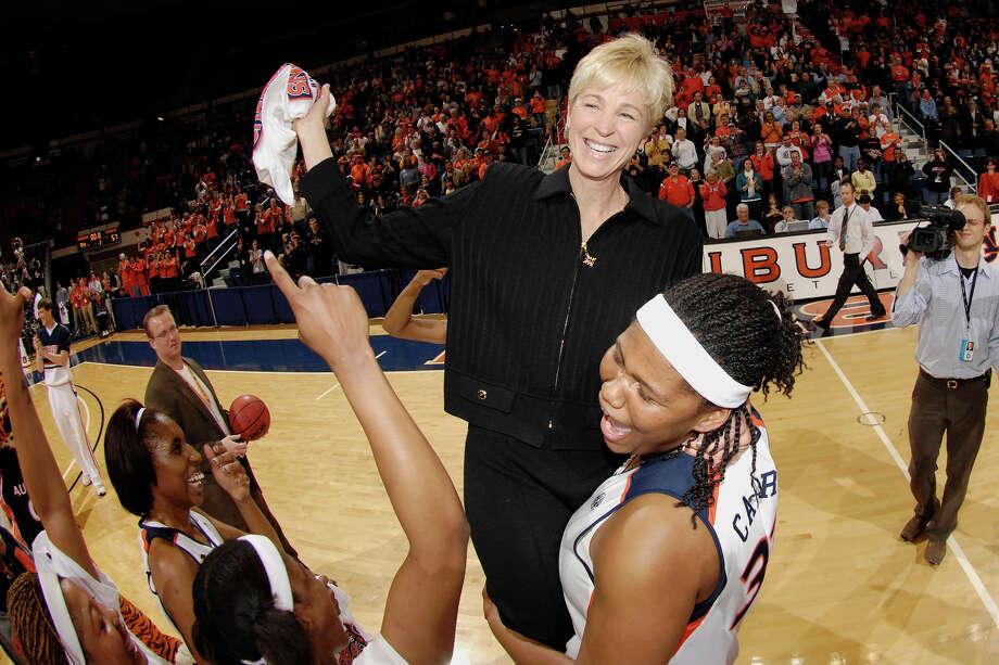 Auburn's KeKe Carrier picks up coach Nell Fortner celebrating the SC Championship Sunday.  Arkansas vs Auburn women's basketball on Sunday, March 1, 2009 in Auburn, Ala.  Todd Van Emst Photo: Todd J. Van Emst