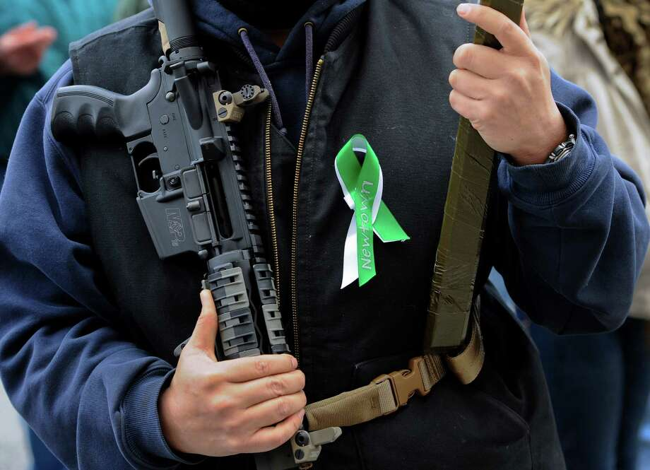 "A man who refused to be identified holds an AR-15 semi-automatic riffle at rally in support for gun rights at the Capitol in Hartford, Conn., Saturday, Jan. 19, 2013.  The rally, dubbed, ""Guns Across America"", at Connecticut's state Capitol and state capitol buildings across the country  to raise concerns about possible new gun legislation that could affect gun owners' rights in the wake of the Dec. 14 school shooting at Sandy Hook Elementary School in Newtown. Photo: Jessica Hill, Associated Press / FR125654 AP"