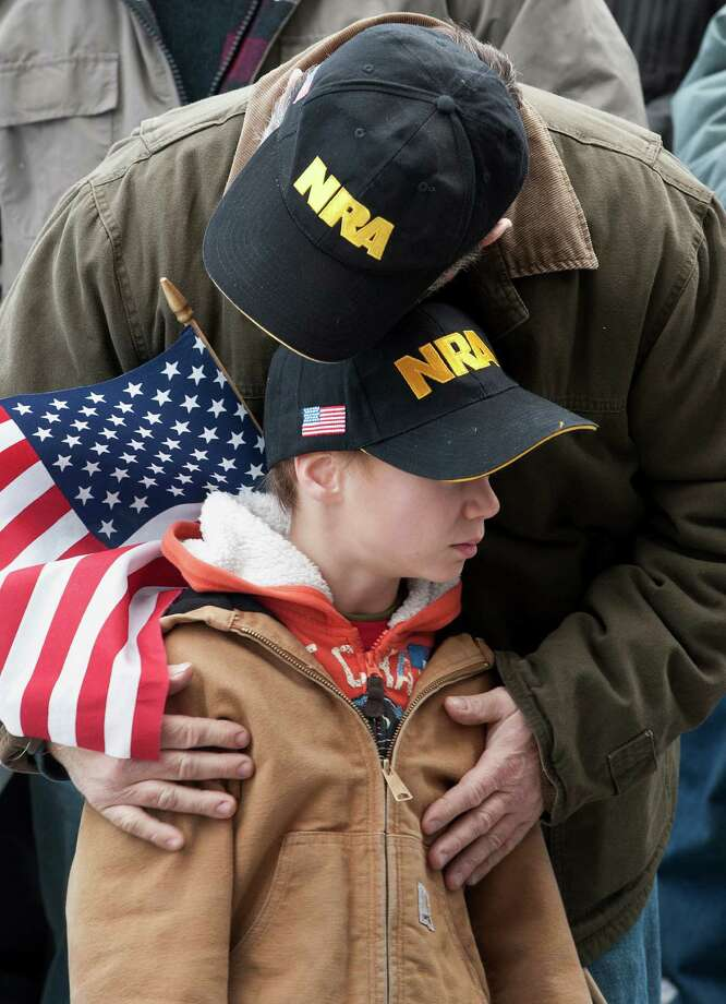 Gun rights supporter Kenny Deal of Stafford, Conn., hugs his son Daniel, at rally at the Capitol in Hartford, Conn., Saturday, Jan. 19, 2013. Photo: Jessica Hill, Associated Press / FR125654 AP
