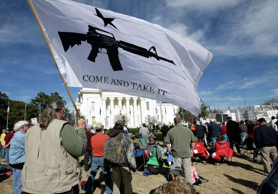 Several hundred people gather on the lawn of the Capitol in Montgomery, Ala., for a rally against gun control on Saturday, Jan. 19, 2013. James Wilson of Elmore, Ala., joined the crowd with his father, and proudly carried his Come and Take It flag. Photo: Dave Martin, Associated Press / AP