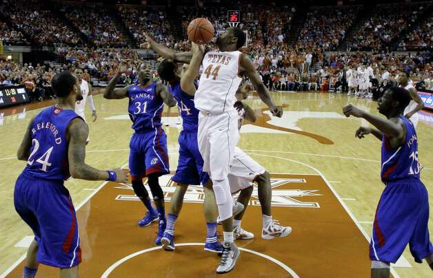 Texas' Prince Ibeh (44) is blocked by Kansas' Perry Ellis (34) as he tries to score during the first half of an NCAA college basketball game, Saturday, Jan. 19, 2013, in Austin, Texas. (AP Photo/Eric Gay) Photo: Eric Gay, Associated Press / AP