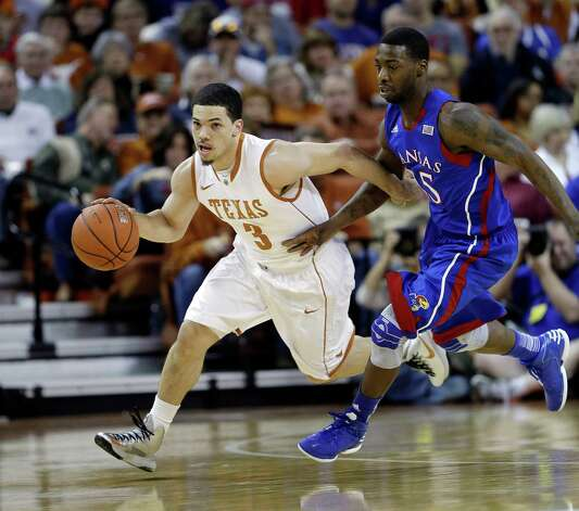Texas' Javan Felix (3) drives the ball past Kansas' Elijah Johnson, right, during the first half of an NCAA college basketball game, Saturday, Jan. 19, 2013, in Austin, Texas. (AP Photo/Eric Gay) Photo: Eric Gay, Associated Press / AP