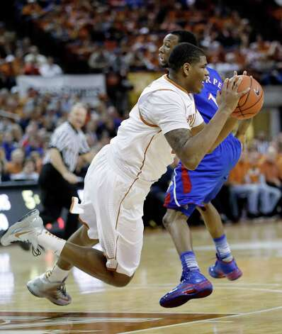 Texas' Cameron Ridley, right, is tripped up as Kansas' Naadir Tharpe, right, defends during the first half of an NCAA college basketball game, Saturday, Jan. 19, 2013, in Austin, Texas. (AP Photo/Eric Gay) Photo: Eric Gay, Associated Press / AP