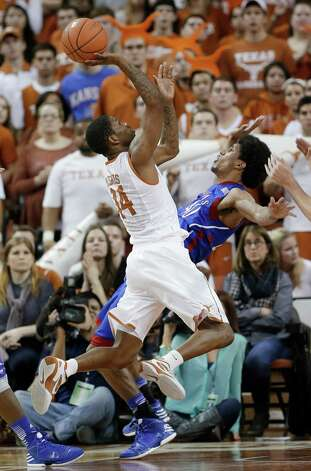 Texas' Julien Lewis (14) crashes into Kasas defender Kevin Young (40) during the second half of an NCAA college basketball game, Saturday, Jan. 19, 2013, in Austin, Texas. Kansas won 64-59. (AP Photo/Eric Gay) Photo: Eric Gay, Associated Press / AP
