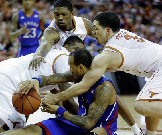 Kansas' Travis Releford, center, battles Texas defenders Cameron Ridley, left, Jonathan Holmes, top center, and Javan Felix (3) for a loose ball during the second half of an NCAA college basketball game, Saturday, Jan. 19, 2013, in Austin, Texas. Kansas won 64-59. (AP Photo/Eric Gay) Photo: Eric Gay, Associated Press / AP