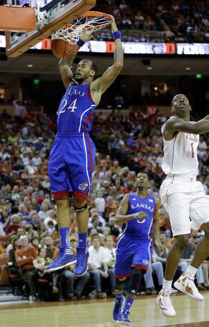 Kansas' Travis Releford (24) scores as Texas' Sheldon McClellan defends during the second half of an NCAA college basketball game, Saturday, Jan. 19, 2013, in Austin, Texas. Kansas won 64-59. (AP Photo/Eric Gay) Photo: Eric Gay, Associated Press / AP