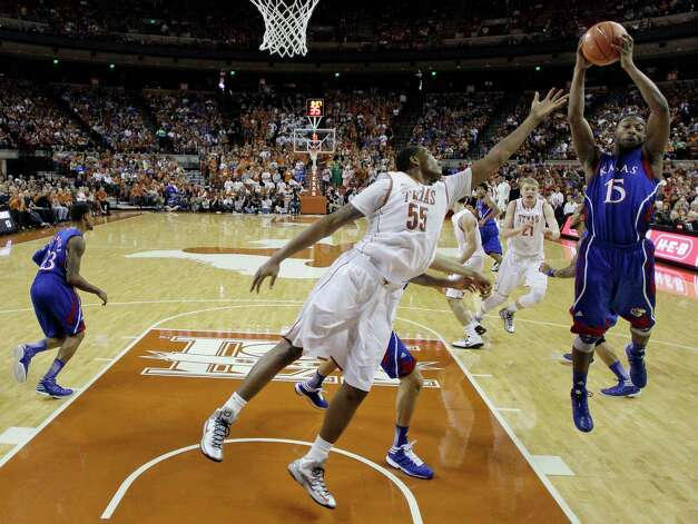 Texas' Cameron Ridley (55) and Kansas' Elijah Johnson (15) leap for a rebound during the first half of an NCAA college basketball game, Saturday, Jan. 19, 2013, in Austin, Texas. (AP Photo/Eric Gay) Photo: Eric Gay, Associated Press / AP