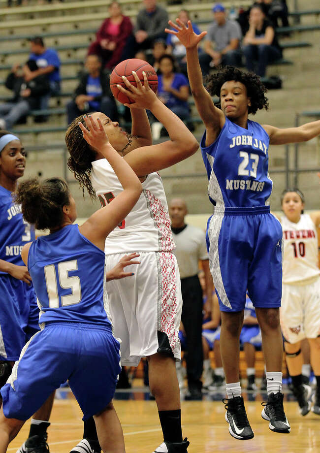 Stevens' Deleesha Monroe (25) shoots under pressure from Jays' Ashia McLaurin (23) and Katelyn McCullar (15)during girls basketball at Paul Taylor Fieldhouse on Saturday, Jan. 19, 2013. Jay defeated Stevens in overtime, 51-47. Photo: Kin Man Hui, Express-News / © 2012 San Antonio Express-News