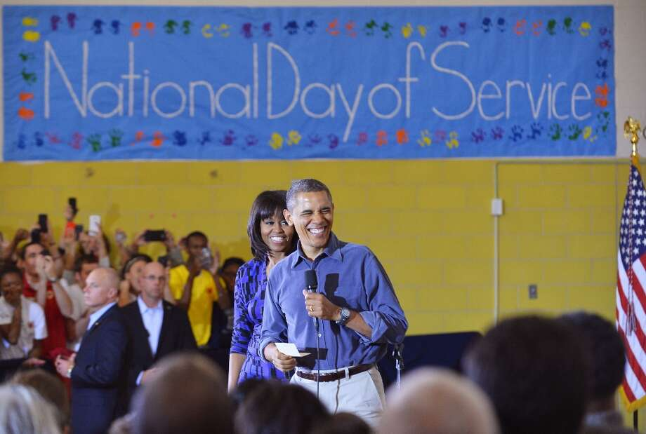US President Barack Obama and First Lady Michelle Obama greet a crowd of people at Burrville Elementary School after participating in National Day of Service on January 19, 2013 in Washington DC, as part of the 57th Presidential Inauguration. Americans across the country participate in service projects in their communities to celebrate the legacy of civil rights leader Dr. Martin Luther King, Jr. The holiday honoring King will be observed on January 21, the day of the second inauguration of US President Barack Obama and Vice President Biden. Photo: JEWEL SAMAD, AFP/Getty Images / AFP