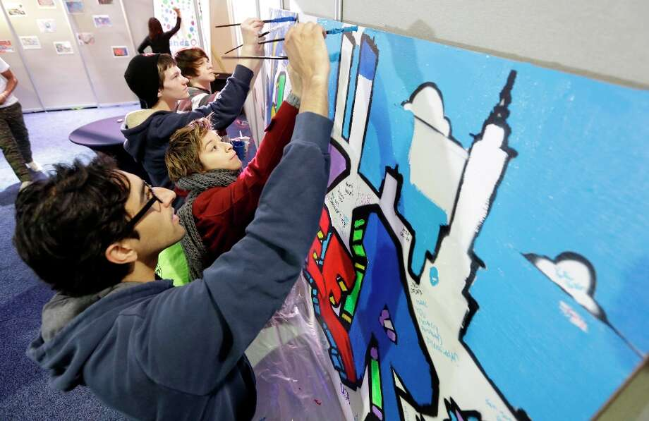 Jay Desai, of Washington, front and Ariel Timar, of Cherry Hill, N.J., center, paint a mural as they participate in the National Day of Service on the Mall as part of the 57th Presidential Inaugural festivities, Saturday, Jan. 19, 2013, in Washington, . The two were working on the Greater DC care project that will place the murals in schools and fire stations to help promote volunteerism. Photo: Steve Helber, Associated Press / AP