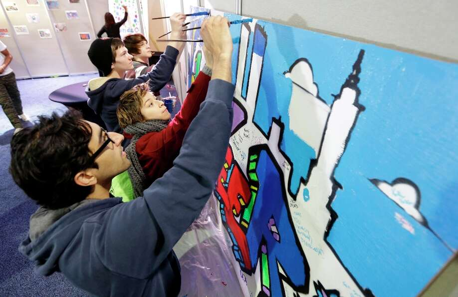 Jay Desai, of Washington, front and Ariel Timar, of Cherry Hill, N.J., center, paint a mural as they