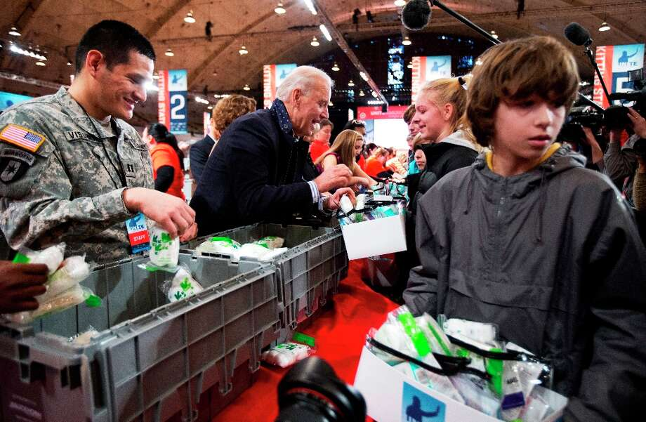 Vice President Joe Biden, center, fills care kits with necessities for deployed U.S. service members, wounded warriors, veterans and first responders, joining the National Day of Service as part of the 57th presidential inauguration in Washington, Saturday, Jan. 19, 2013. Volunteer Nathan Fouse walks with a care kit at right. Photo: Manuel Balce Ceneta, Associated Press / AP