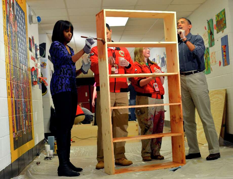 President Barack Obama, right, first lady Michelle Obama, left,  City Year Executive Director Jeff Franco, City Year and City Year employee Sheri Fisher, second from right, stain a bookshelf at Burrville Elementary School in Washington, Saturday, Jan. 19, 2013, as the first family participated in a community service project for the National Day of Service as part of the 57th Presidential Inauguration. Photo: Susan Walsh, Associated Press / AP