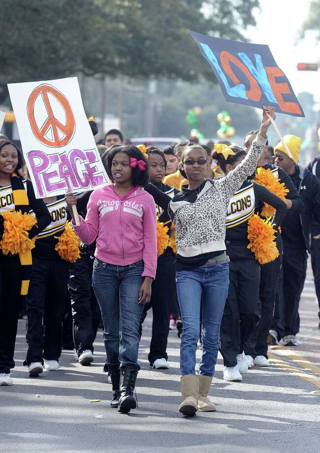 Two girls hold Peace and Love signs while walking with the Austin Middle School Falcon cheerleaders during the Martin Luther King, Jr. parade on Highland Avenue in Beaumont on Saturday, January, 19, 2013. Photo taken: Randy Edwards/The Enterprise Photo: Randy Edwards