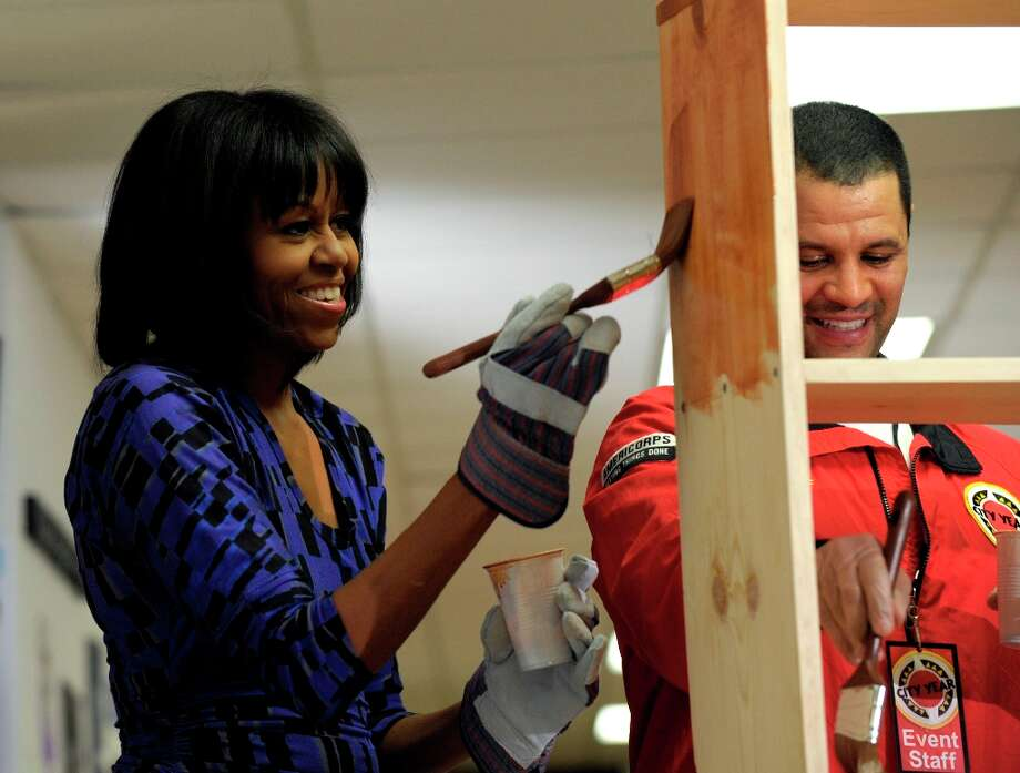 ADD NAMES - First lady Michelle Obama, accompanied by Jeff Franco, executive director of City Year, stains a bookshelf at Burrville Elementary School in Washington, Saturday, Jan. 19, 2013, as the first family participated in a community service project for the National Day of Service, part of the 57th Presidential Inauguration. Photo: Susan Walsh, Associated Press / AP