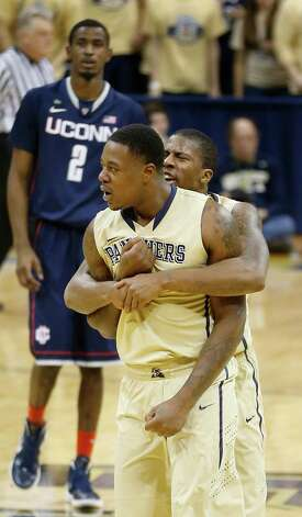 Pittsburgh's Lamar Patterson, right, hugs Dante Taylor after Taylor hit a jump shot against Connecticut during the second half of an NCAA college basketball game, Saturday, Jan. 19, 2013, in Pittsburgh. Connecticut's DeAndre Daniels (2) watches in the background. Pittsburgh won 69-61. (AP Photo/Keith Srakocic) Photo: Keith Srakocic, Associated Press / AP
