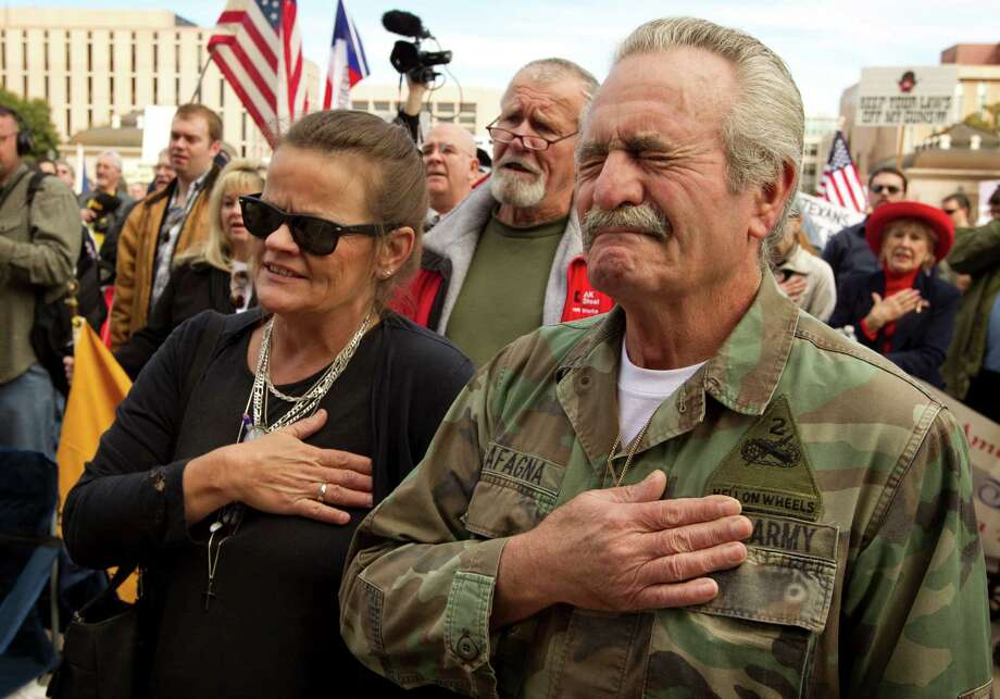 Rafael Cafagna, of Killeen, Texas, fights back tears during the singing of the national anthem at the Guns Across America rally at the Capitol in Austin, Texas, Saturday, January 19, 2013. At left is Rafael's wife, Shannon Cafagna. Photo: Jay Janner, McClatchy-Tribune News Service / Austin American-Statesman